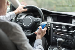 Man using a smartphone and driving Royalty Free Stock Photo