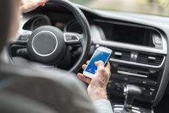Man using a smartphone and driving Royalty Free Stock Image