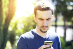 Man using smartphone. Man using smartphone in garden royalty free stock image