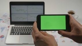 Man using smartphone with green screen chroma key on white office table with laptop on background. Top view. Male hands. Close up man holding smartphone touch stock footage
