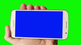 Man  Using Smartphone with Green Screen. Closeup of a smart phone with blue screen in the hand of man. Man finger touches the screen. Isolated stock video footage