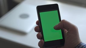 Man using smartphone. With green screen in home stock footage