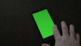 The man is using a smartphone with a green screen that lies on the table. 4K stock video footage