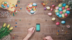Man using smartphone with green screen on table decorated with easter eggs. Top view. Stock footage of Man using smartphone with green screen on table decorated stock video