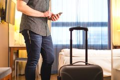 Man using smartphone in hotel room with baggage and suitcase. stock images