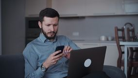 Man using smartphone and laptop at home stock footage