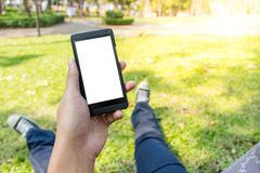 Man using smartphone. Lay down at park in the morning, first eye view Royalty Free Stock Images