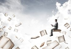 Man using smartphone and many books flying in air. Young businessman floating in blue sky with smartphone in hands Royalty Free Stock Photography