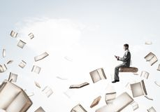 Man using smartphone and many books flying in air. Young businessman floating in blue sky with smartphone in hands Stock Photography