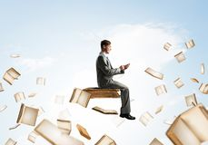 Man using smartphone and many books flying in air. Young businessman floating in blue sky with smartphone in hands Stock Photo
