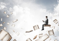 Man using smartphone and many books flying in air. Young businessman floating in blue sky with smartphone in hands Stock Photos