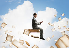 Man using smartphone and many books flying in air. Young businessman floating in blue sky with smartphone in hands Royalty Free Stock Photos