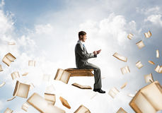 Man using smartphone and many books flying in air. Young businessman floating in blue sky with smartphone in hands Royalty Free Stock Images
