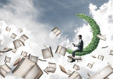 Man using smartphone and many books flying in air. Young businessman floating on green moon in blue sky with smartphone in hands Royalty Free Stock Photos
