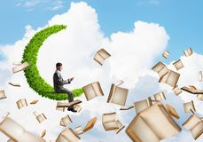 Man using smartphone and many books flying in air. Young businessman floating on green moon in blue sky with smartphone in hands Stock Images