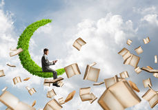 Man using smartphone and many books flying in air. Young businessman floating on green moon in blue sky with smartphone in hands Stock Image