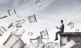 Man using smartphone and many books flying in air Stock Photography