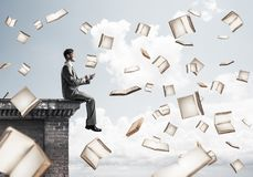 Man using smartphone and many books flying in air. Young businessman sitting on building edge with smartphone in hands Stock Photography