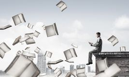 Man using smartphone and many books flying in air. Young businessman sitting on building edge with smartphone in hands Royalty Free Stock Photo