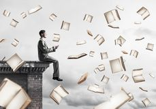 Man using smartphone and many books flying in air. Young businessman sitting on building edge with smartphone in hands Royalty Free Stock Photos