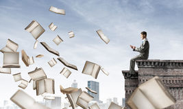 Man using smartphone and many books flying in air Royalty Free Stock Photography