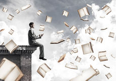 Man using smartphone and many books flying in air Stock Photo