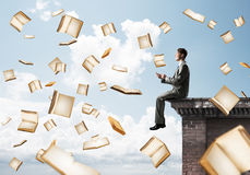 Man using smartphone and many books flying in air Royalty Free Stock Photo