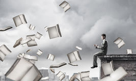 Man using smartphone and many books flying in air Royalty Free Stock Photos