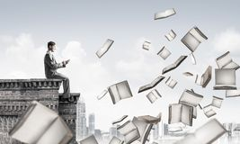Man using smartphone and many books flying in air. Young businessman sitting on building edge with smartphone in hands Stock Photos