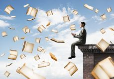 Man using smartphone and many books flying in air. Young businessman sitting on building edge with smartphone in hands Royalty Free Stock Photography