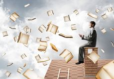 Man using smartphone and many books flying in air. Young businessman sitting on house roof with smartphone in hands Stock Photos