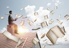 Man using smartphone and many books flying in air. Young businessman sitting on house roof with smartphone in hands Royalty Free Stock Photos