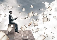 Man using smartphone and many books flying in air. Young businessman sitting on house roof with smartphone in hands Royalty Free Stock Photography