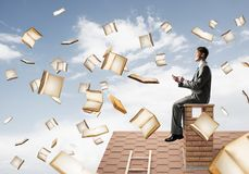 Man using smartphone and many books flying in air. Young businessman sitting on house roof with smartphone in hands Stock Images