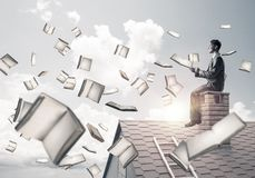 Man using smartphone and many books flying in air. Young businessman sitting on house roof with smartphone in hands Stock Photography