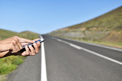 Man using a smartphone next to the road Royalty Free Stock Photo