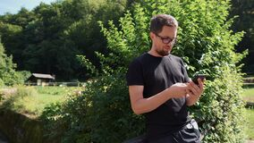 Man is using smartphone outdoors in garden. In sunny day stock footage