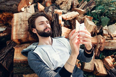 Man using smartphone on pile of wood Stock Photography
