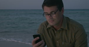 Man Using Smartphone by the Sea. Young man is sitting by the sea and texting message in smartphone in the evening stock video