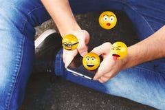 Man using smartphone sending emojis. Royalty Free Stock Photo