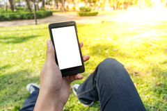 Man using smartphone. Sit with one's knee up chill out at park in the morning, first eye view Royalty Free Stock Photos