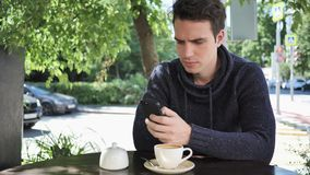 Man using smartphone while sitting in cafe terrace stock video footage