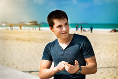 Man using smartphone sitting on the city beach Royalty Free Stock Photos