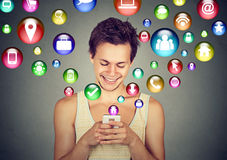Man using smartphone social media application icons flying up Stock Photos