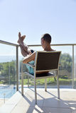 Man using a smartphone and sunbathing in a chair Stock Images