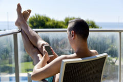 Man using a smartphone and sunbathing in a chair Stock Photography