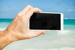 Man using smartphone for taking photo on a beach Stock Photography