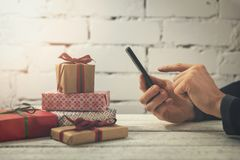 man using smartphone to buy gifts online stock photography