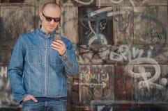 Man using smartphone on urban graffiti background Royalty Free Stock Photo