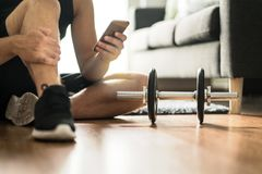 Man using smartphone during workout at home royalty free stock photo